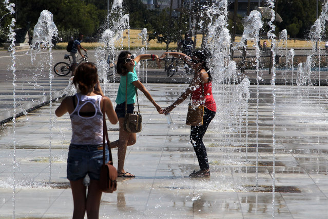 Tourists take photographs of themselves in the middle of water jets in a public fountain at the sea-front, in the northern Greek port of Thessaloniki, Monday, July 7, 2014. Temperatures are predicted to reach 36 degrees Celsius (96.8 Fahrenheit) in Greece. (Photo by Nikolas Giakoumidis/AP Photo)