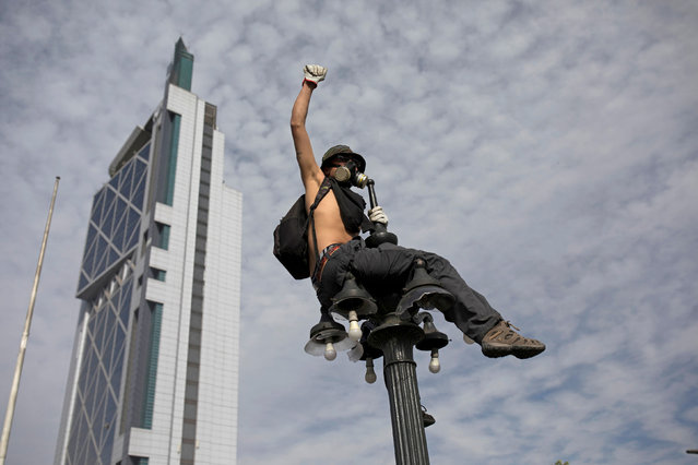 A demonstrator sits on a street light as protests against high living costs continue, in Santiago, Chile on October 22, 2019. (Photo by Pablo Sanhueza/Reuters)