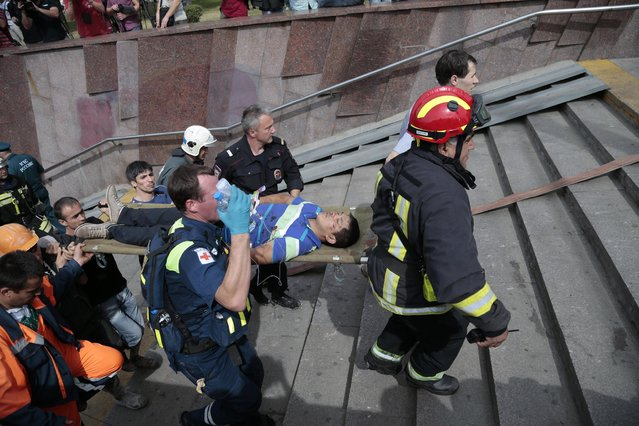 Paramedics, a police officer and a volunteer carry an injured man out from a subway station after a rush-hour subway train derailment in Moscow, Russia, on Tuesday, July 15, 2014. (Photo by Ivan Sekretarev/AP Photo)