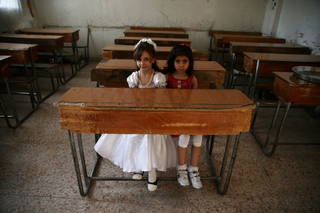 Girls sit inside an empty classroom as they pose for a photograph during a celebration marking the end of the school year in the town of Douma, eastern Ghouta in Damascus, Syria May 21, 2016. (Photo by Bassam Khabieh/Reuters)