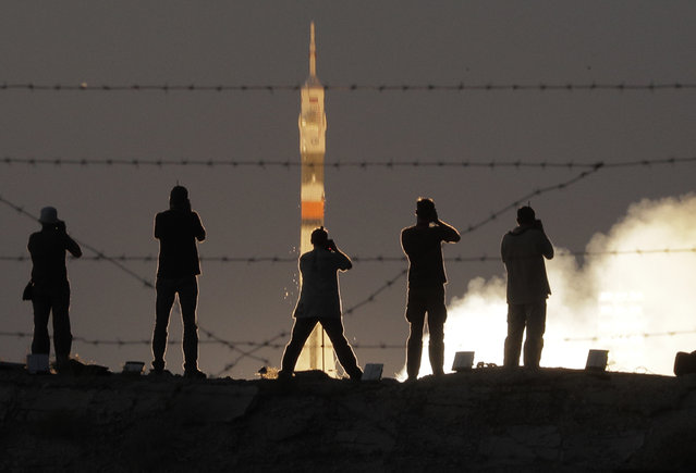 Photographers take photos of the Soyuz-FG rocket booster with Soyuz MS-05 space ship carrying a new crew to the International Space Station, ISS, blasting off at the Russian leased Baikonur cosmodrome, Kazakhstan, Friday, July 28, 2017. The Russian rocket carries U.S. astronaut Randy Bresnik, Russian cosmonaut Sergey Ryazanskiy and Italian astronaut Paolo Nespoli. (Photo by Dmitri Lovetsky/AP Photo)
