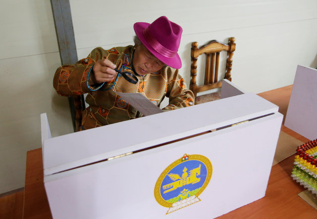 A villager reads her ballot paper before she fills it for the parliamentary elections at a polling station on the outskirt of Ulaanbaatar, Mongolia, June 29, 2016. (Photo by Jason Lee/Reuters)