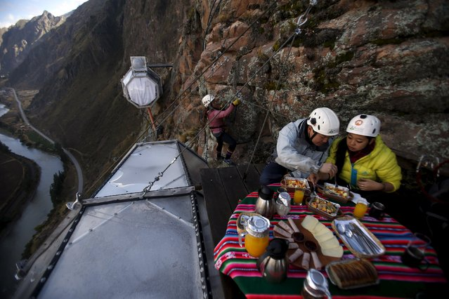 "Guests have breakfast as another guest climbs to gather at the Skylodge Adventure Suites in the Sacred Valley in Cuzco, Peru, August 14, 2015. Tourists taking on an arduous climb up the steep cliff face of Peru's Sacred Valley are being rewarded for their efforts by being able to spend the night in transparent mountaintop sleeping pods at the ""Skylodge Adventure Suites"". (Photo by Pilar Olivares/Reuters)"
