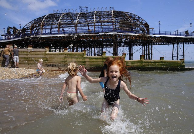 Seven year old Lily Blackburn plays with friends in the sea near the burnt remains of a section of Eastbourne pier, in Eastbourne, southern England July 31, 2014. A Victorian-era seaside pier at Eastbourne on Britain's south coast was badly damaged when fire broke out in an amusement arcade on Wednesday. Flames could be seen leaping from the roof of the two-storey structure as a large plume of smoke rose above the town. (Photo by Luke MacGregor/Reuters)
