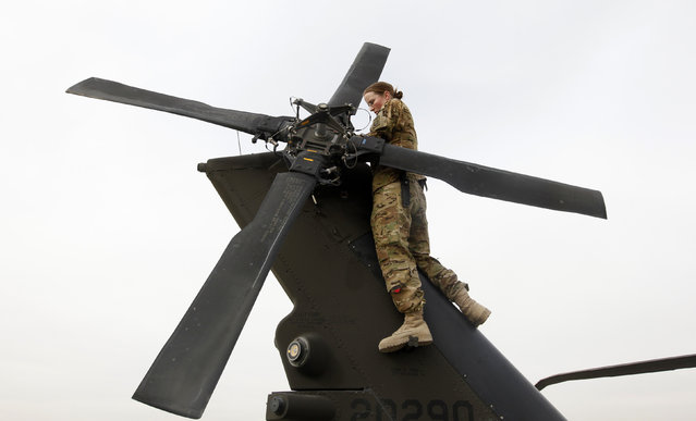 U.S. Army Specialist Nicole Derk of the C Company 3/82 Dustoff MEDEVAC performs a system check on a helicopter at the beginning of her shift in Logar province, eastern Afghanistan, November 21, 2011. (Photo by Umit Bektas/Reuters)