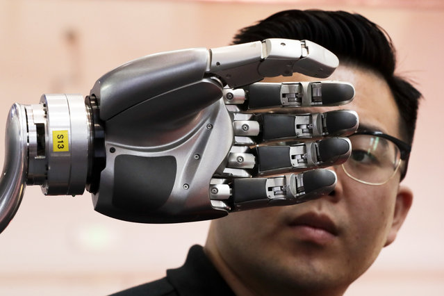 A visitor looks at a robotic hand powered by Kinfinity Glove, developed by the German Aerospace Center, on display at the World Robot Conference at the Yichuang International Conference and Exhibition Centre in Beijing, Wednesday, August 23, 2017. (Photo by Andy Wong/AP Photo)