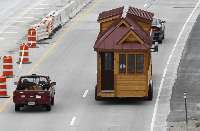 A Tumbleweed brand Cypress 24 model Tiny House is towed down the highway near Boulder, Colorado August 4, 2014. The Tiny House Movement started some years ago with people around the world building really small living spaces and loving their new simplified lives. These tiny houses can range from 1,000 square feet (93 square meters) down to less than 100 square feet (9.3 square meters), and are certainly not ramshackle shacks. (Photo by Rick Wilking/Reuters)