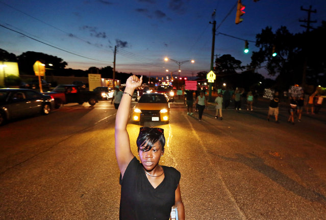 Sirica Bolling raises her fist as she walks down Jefferson Avenue during a Black Lives Matter protest against police brutality in Newport News, Va., Sunday July 10, 2016. (Photo by Aileen Devlin/The Daily Press via AP Photo)