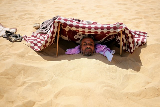 A patient buried in the hot sand looks out from under a shade that protects his face from the sun in Siwa, Egypt, August 12, 2015. (Photo by Asmaa Waguih/Reuters)