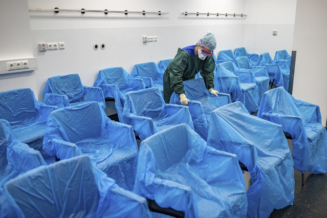 A nurse assembles plastic-wrapped chairs in a waiting area in the central emergency room of the University Hospital in Essen, Germany, Monday, March 23, 2020. The University Hospital in Essen has specially adapted to patients who have fallen ill with the coronavirus. (Photo by Marcel Kusch/dpa via AP Photo)