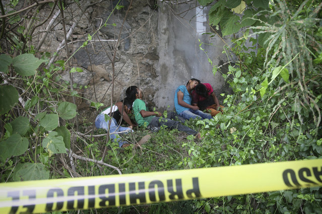The bodies of four men, two of them teenagers, lie against a wall under an overpass on a highway after being shot in the town of Coyuca, near Acapulco, Guerrero state, Mexico, Tuesday, September 12, 2017. The position of the bodies suggested they were lined up and shot, according the Guerrero state security spokesman Roberto Alvarez. (Photo by Bernandino Hernandez/AP Photo)