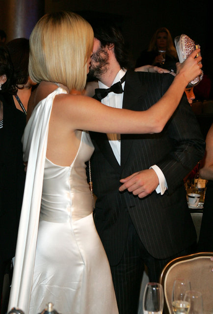 Actors Charlize Theron and Keanu Reeves kiss during the 20th Annual American Cinematheque Award dinner honoring Al Pacino at the Beverly Hilton Hotel on October 21, 2005 in Beverly Hills, California. (Photo by Frazer Harrison)