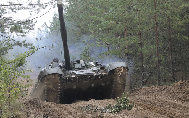 In this photo taken on Friday, September 15, 2017, Belarusian army tank drives during the war games at an undisclosed location in Belarus. Russia and Belarus began major war games Thursday, an operation involving thousands of troops, tanks and aircraft on NATO's eastern edge practicing how to hunt down and destroy armed spies, among other maneuvers. (Photo by Vayar Military Agency Photo via AP Photo)