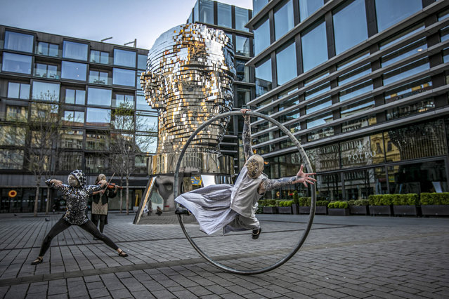 Members of the contemporary circus company Cirk La Putyka perform in front of sculpture of Franz Kafka's head to entertain local residents in Prague, Czech Republic, 21 April 2020. The aim of the Cirk La Putyka events in the streets of Czech capital is to get live art back to people during the lockdown. According to them, when people can't go to the artists, to the theater, the actors go to the people. The Czech government has imposed a lockdown in an attempt to slow down the spread of the pandemic COVID-19 disease caused by the SARS-CoV-2 coronavirus. (Photo by Martin Divisek/EPA/EFE/Rex Features/Shutterstock)