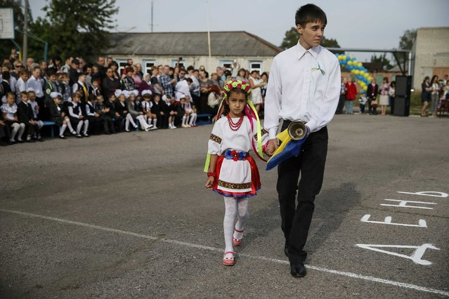 First graders attend a festive ceremony to mark the start of another school year in Slaviansk, September 1, 2014. (Photo by Gleb Garanich/Reuters)