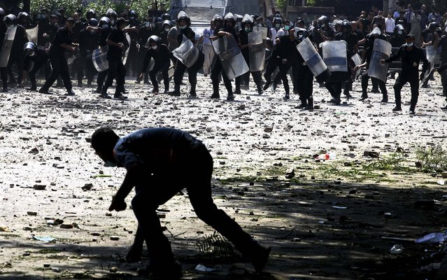 A protester and police throw stones at each other during clashes in Cairo. For all the harrowing images of the deadly attack on the American mission in Benghazi, Libya, and the American Embassy in Cairo coming under siege from protesters Tuesday, the Obama administration is grappling with the possibility that its far bigger long-term problem lies in Egypt, not Libya. (Photo by Tara Todras-Whitehill/The New York Times)
