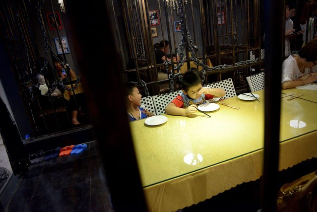This picture taken on September 9, 2014 shows a family preparing to have dinner at a prison themed restaurant in Tianjin. (Photo by Wang Zhao/AFP Photo)