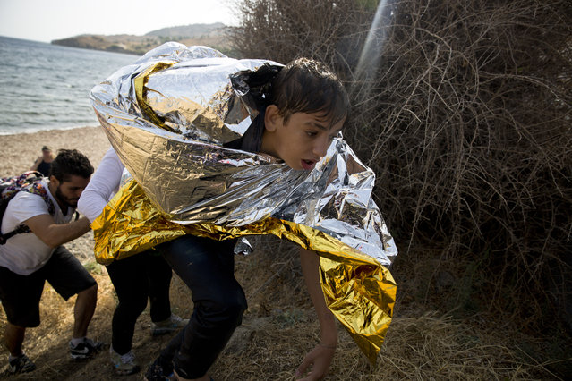 A young Syrian boy, wrapped with a thermal blanket, arrives with others after crossing aboard a dinghy from Turkey, on the island of Lesbos, Greece, Monday, Sept. 7, 2015. (Photo by Petros Giannakouris/AP Photo)