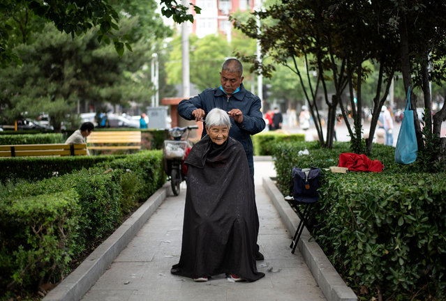 A barber cuts the hair of an elderly woman at a public park in Beijing on May 13, 2020. (Photo by Noel Celis/AFP Photo)