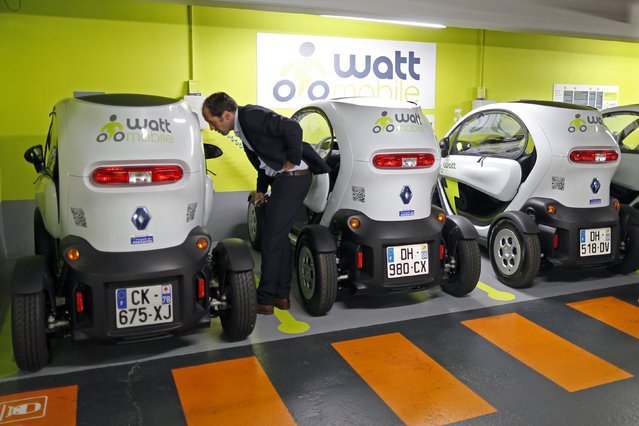 A man looks at a Twizy, the Renault electric city car, during a presentation of the Wattmobile, a new self-drive Autolib-style electric car service at Gare de l'Est train station in Paris September 18, 2014. Wattmobile and SNCF railways offer Renault electric cars and Peugeot e-Vivacity electric scooters rentals from Paris, Marseille, Lyon and Lille train stations. The network will grow to 20 train stations in France by the end of the year. (Photo by Charles Platiau/Reuters)