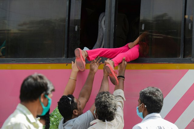 Passengers board children through the window of a bus as Telangana State Road Transport Corporation (TSRTC) resumed bus services after the government eased a nationwide lockdown imposed as a preventive measure against the COVID-19 coronavirus, at Jubilee Bus Station (JBS) in Secunderabad, the twin city of Hyderabad on May 20, 2020. (Photo by Noah Seelam/AFP Photo)