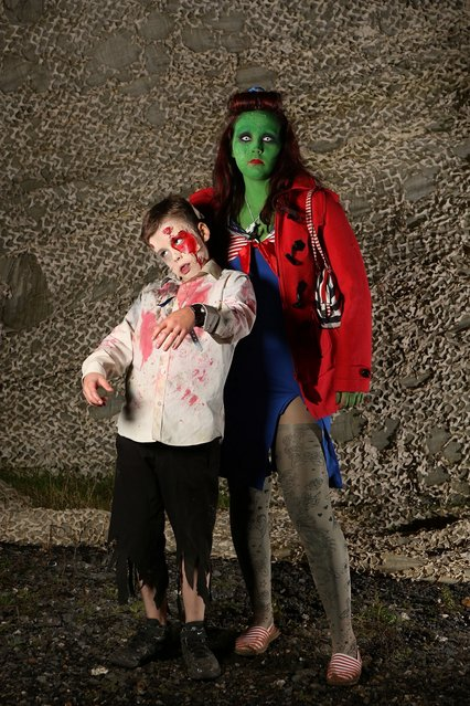 A mother and her son dress as zombies at the Shocktober Fest at Tulleys Farm on October 6, 2012 in Turners Hill, England. People dressed as zombies from around the United Kingdom have converged on Tulleys Farm in an attempt to set a new Guinness World Record for the most zombies together in one place.  (Photo by Peter Macdiarmid)