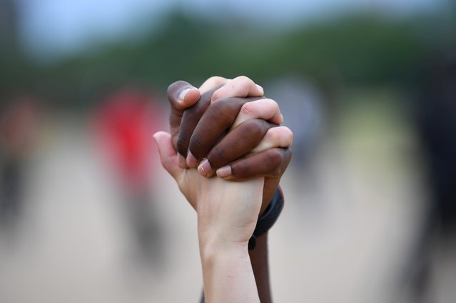 """A man and a woman hold hands aloft in Hyde Park during a """"Black Lives Matter"""" protest following the death of George Floyd who died in police custody in Minneapolis, London, Britain, June 3, 2020. (Photo by Dylan Martinez/Reuters)"""