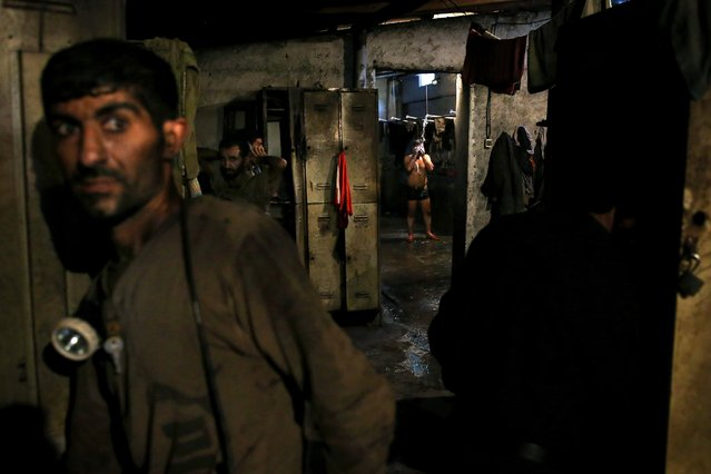 In this Tuesday, May 6, 2014 photo, an Iranian coal miner takes a shower while others prepare to go home after a long day of work at a mine on a mountain in Mazandaran province, near the city of Zirab, 212 kilometers (132 miles) northeast of the capital Tehran Iran. Around 1,200 miners work across 10 mines in the Mazandaran province, in a mountainous, verdant area. More than 12,000 tons of coal is extracted from the mines each month, almost all of which is shipped south for use in Iran's steel industry. (Photo by Ebrahim Noroozi/AP Photo)