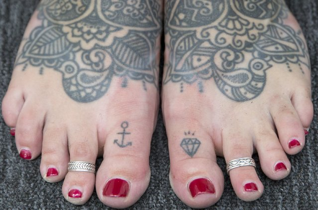 A woman shows her tattooed feet during the 10th International Tattoo Convention in London September 27, 2014. (Photo by Neil Hall/Reuters)