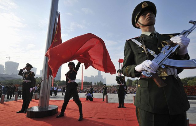 A paramilitary policeman spreads a Chinese national flag during a flag-raising ceremony to mark the 65th anniversary of the founding of the People's Republic of China, in Hefei, Anhui province October 1, 2014. (Photo by Reuters/Stringer)