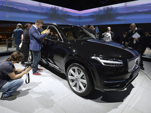 People take pictures of the new Volvo XC90 at the 2014 Paris Auto Show on October 2, 2014 in Paris, on the first of the two press days. (Photo by Miguel Medina/AFP Photo)
