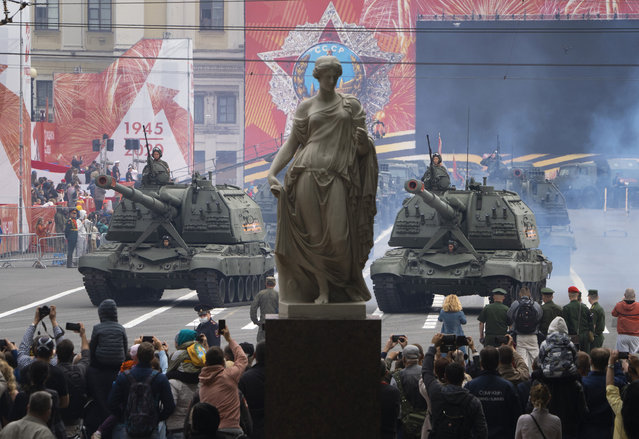 People take photos as self-propelled artillery vehicles  Msta-S travel during a rehearsal for a military parade at Dvortsovaya (Palace) Square in St.Petersburg, Russia, Saturday, June 20, 2020. The military parade marking the 75th anniversary of the Nazi defeat was postponed from May 9 due to the outbreak of the coronavirus pandemic and is now set to take place on June 24.(Photo by Dmitri Lovetsky/AP Photo)