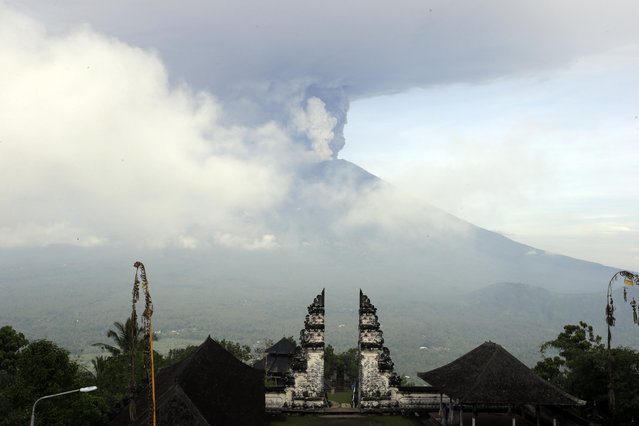 Clouds of ashes raise from the Mount Agung volcano erupting in Karangasem, Indonesia, Monday, November 27, 2017. (Photo by Firdia Lisnawati/AP Photo)