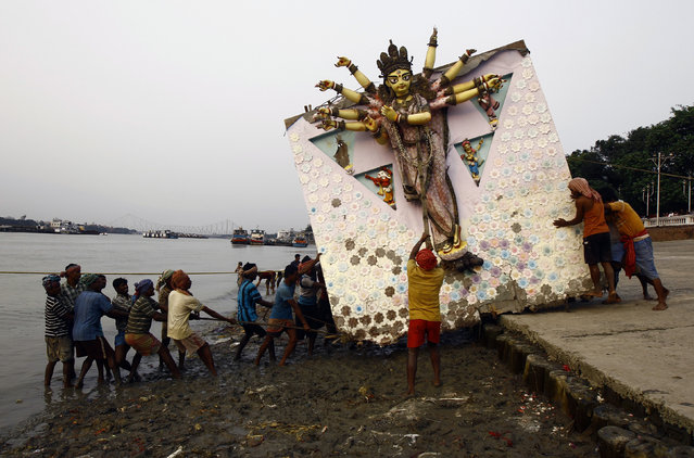 Hindu devotees pull an idol of the Hindu goddess Durga for immersion into the Ganges river in Kolkata October 3, 2014. (Photo by Rupak De Chowdhuri/Reuters)