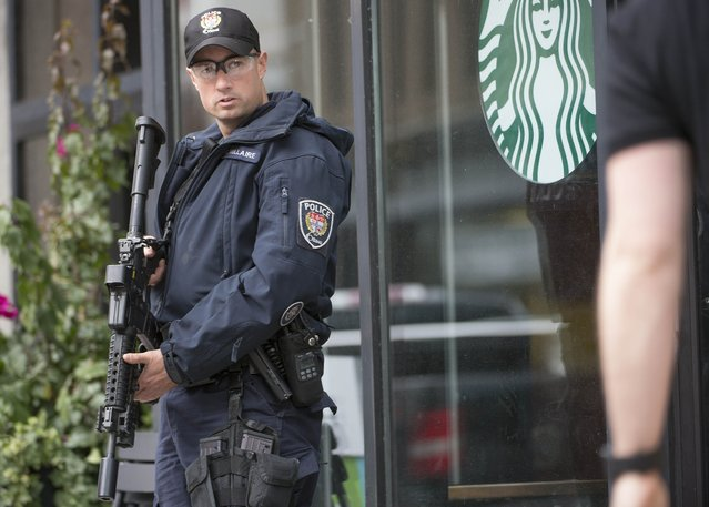 An police officer stands watch outside a Starbucks in Ottawa,Ontario after multiple shootings on October 22, 2014. Gunfire echoed through the Gothic halls of the Canadian parliament Wednesday as police shot dead a gunman suspected of killing a soldier guarding a nearby war memorial before storming the building. Police said an investigation was continuing, but did not confirm earlier reports that more gunmen were involved. Heavily armed officers backed by armored vehicles sealed off the building. (Photo by Peter McCabe/AFP Photo)