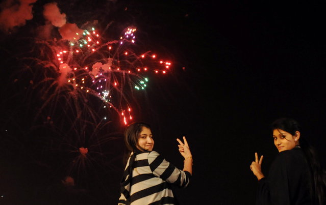 Pakistani girls pose for a photograph during a fireworks display at Clifton Beach in Karachi to celebrate the New Year early on January 1, 2013. (Photo by Asif Hassan/AFP Photo)