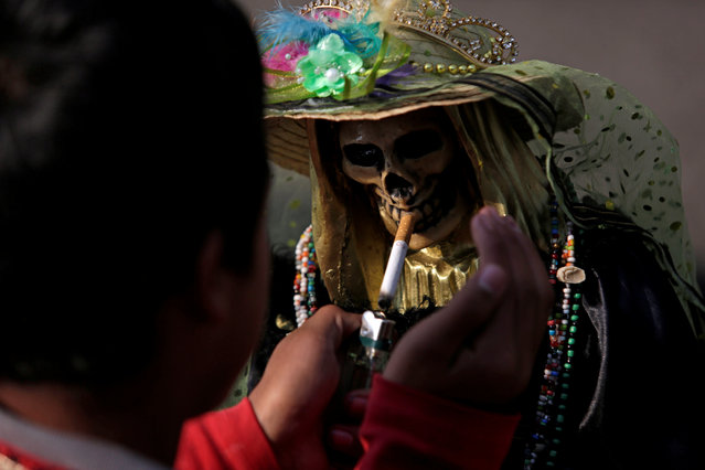 A devotee lights a cigaret to a figure of Santa Muerte or The Saint of Death during the first prayer of the New Year at Tepito neighborhood in Mexico City on January 1, 2018. (Photo by Daniel Becerril/Reuters)