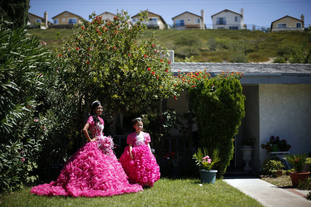 Mimi Pineda, 15, whose parents are from El Salvador, stands outside her aunt's house with Maybelin Ramirez, 6, before her quinceanera in Santa Clarita, California August 23, 2014. (Photo by Lucy Nicholson/Reuters)