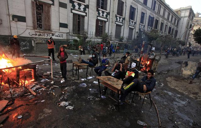 Egyptian protesters sit at school desks taken from a nearby vandalized school during clashes with riot police near Tahrir Square, on January 26, 2013. (Photo by Khalil Hamra/AP Photo/The Atlantic)
