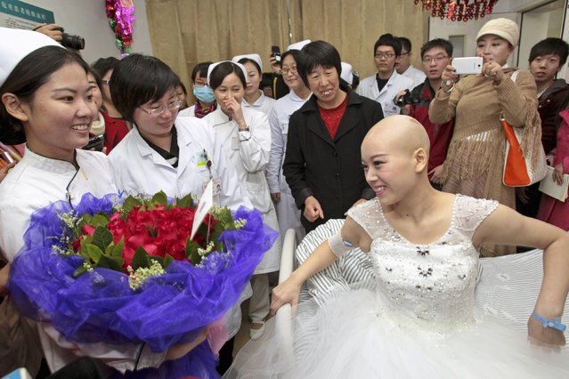 Bride Fan Huixiang (front R), a 25-year-old cancer patient, receives flowers from nurses on her bed before her wedding ceremony at a hospital in Zhengzhou, Henan province November 17, 2014. Fan was diagnosed with late stage adenocarcinoma, a type of cancerous tumor, at her thoracic vertebra this June. (Photo by Reuters/China Daily)