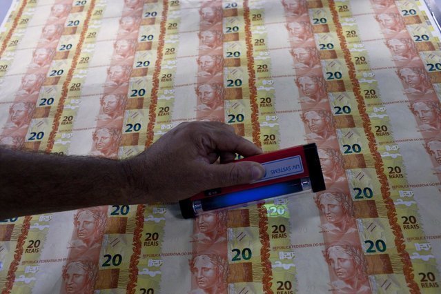 A worker checks the security feature on prints of R$ 20 Brazilian reais bills during the production process at the Casa da Moeda, the national mint, in the Santa Cruz suburb of Rio de Janeiro, Brazil, on Tuesday, March 5, 2013. Brazil is likely to keep its key interest rate at a record low for the third straight meeting, as policy makers are caught between a fragile economic recovery and faster-than-expected inflation. (Photo by Dado Galdieri/Bloomberg)