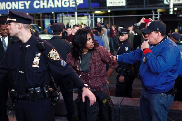 A protester is detained by a New York Police Department (NYPD) officer in Times Square during a rally in New York, November 24, 2014, after the grand jury decided not to indict a Ferguson police officer in the death of 18-year-old Michael Brown in Missouri. (Photo by Eduardo Munoz/Reuters)