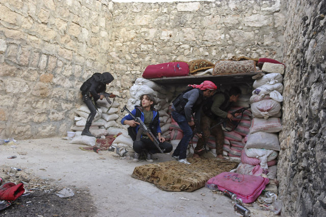 Rebel fighters take up position behind piles of sandbags on the Karm al-Tarab frontline, next to Aleppo International airport November 23, 2014. (Photo by Abdalrhman Ismail/Reuters)