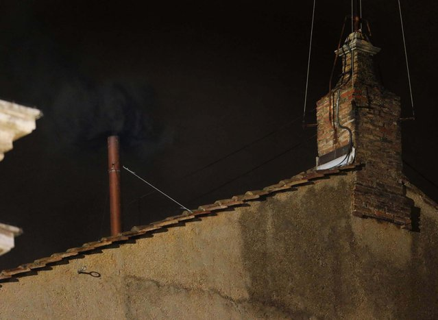 Black smoke emerges from the chimney on the roof of the Sistine Chapel, indicating that the cardinals did not elect a new pope on March 12, 2013. (Photo by Dmitry Lovetsky/Associated Press)