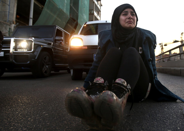 The sister of Lebanese soldier Ali Bazzal, who was kidnapped by Islamic State militants, cries as she sits on the ground blocking a main road, after Nusra Front released this afternoon a picture for her brother with a sword points on his neck threatened to kill him within hours if Lebanese authorities do not release a woman that is being held over terrorism charges, as she protests demanding that the government negotiate with the militants, in downtown Beirut, Lebanon, Friday, November 28, 2014. (Photo by Hussein Malla/AP Photo)