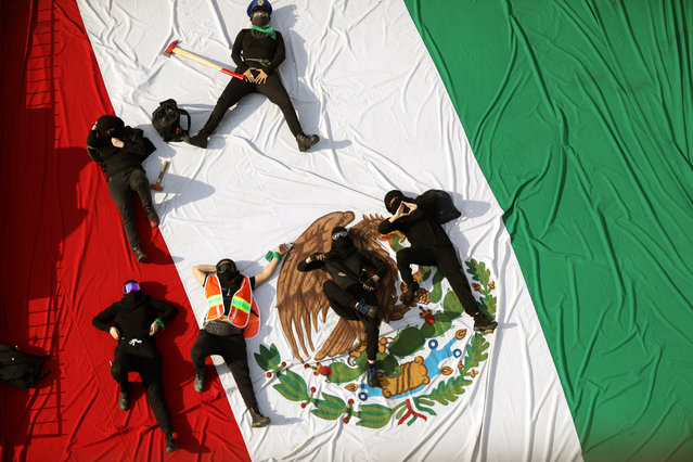 Activists lie on a Mexican flag at the National Polytechnic Institute in Mexico City, Mexico, 10 October 2020. People protesting for women's rights occupied a campus of the National Polytechnic Institute (IPN) to demand justice for harassment in the facility, including the rape of a student. (Photo by Sashenka Gutierrez/EPA/EFE)