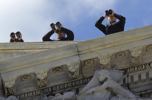 Security personnel atop the U.S. Capitol scan the area with their binoculars before U.S. President Barack Obama and Irish Prime Minister Enda Kenny walk down the east steps after attending the Friends of Ireland luncheon in Washington March 19, 2013. (Photo by Gary Cameron/Reuters)