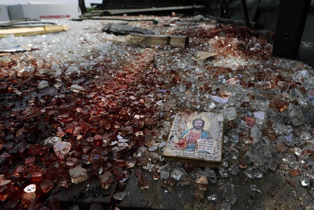 A bloodstained icon of Jesus is seen amidst blood-soaked shattered glass atop a wrecked truck near the Donetsk airport, in this May 27, 2014 file photo. (Photo by Yannis Behrakis/Reuters)