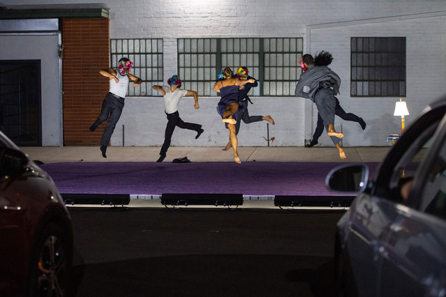 """Dancers from """"LA Dance Project"""" perform, wearing a mask, during the drive-in show """"Solo at Dusk"""" in Los Angeles, California, on October 13, 2020, amid the Coronavirus pandemic. (Photo by Valerie Macon/AFP Photo)"""