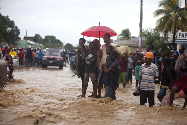 People stand in a street flooded by a nearby river overflowing from the heavy rains caused by Hurricane Matthew, in Leogane, Haiti, Wednesday, October 5, 2016. (Photo by Dieu Nalio Chery/AP Photo)